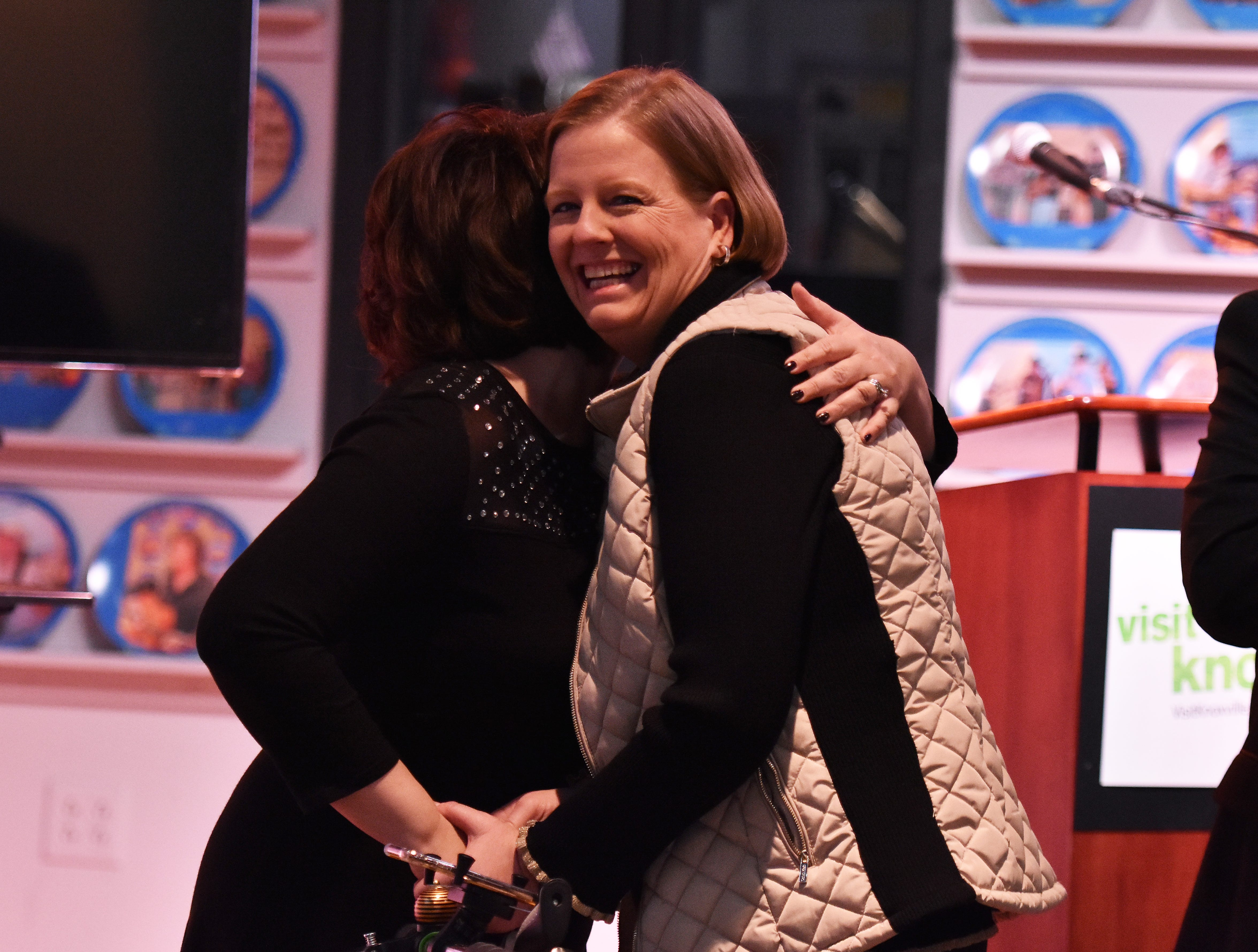 Kim Bumpas, right, president of Visit Knoxville, receives a hug from Lanna Smith prior to the press conference.