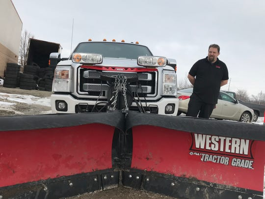 Lonnie Barnett stands in front of his V snow plow blade. Barnett has slowly built a client base of 30 restaurant parking lots, apartment complexes and private properties that pay him to plow.