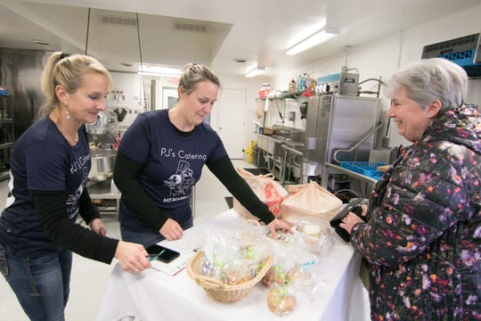 From left, Pam Russell and Jody Seagraves of PJ's Catering work with customer Molly Canfield of Genoa Township, who picks up a dinner order Friday, Jan. 18, 2019 at the Howell catering and meals-to-go business.