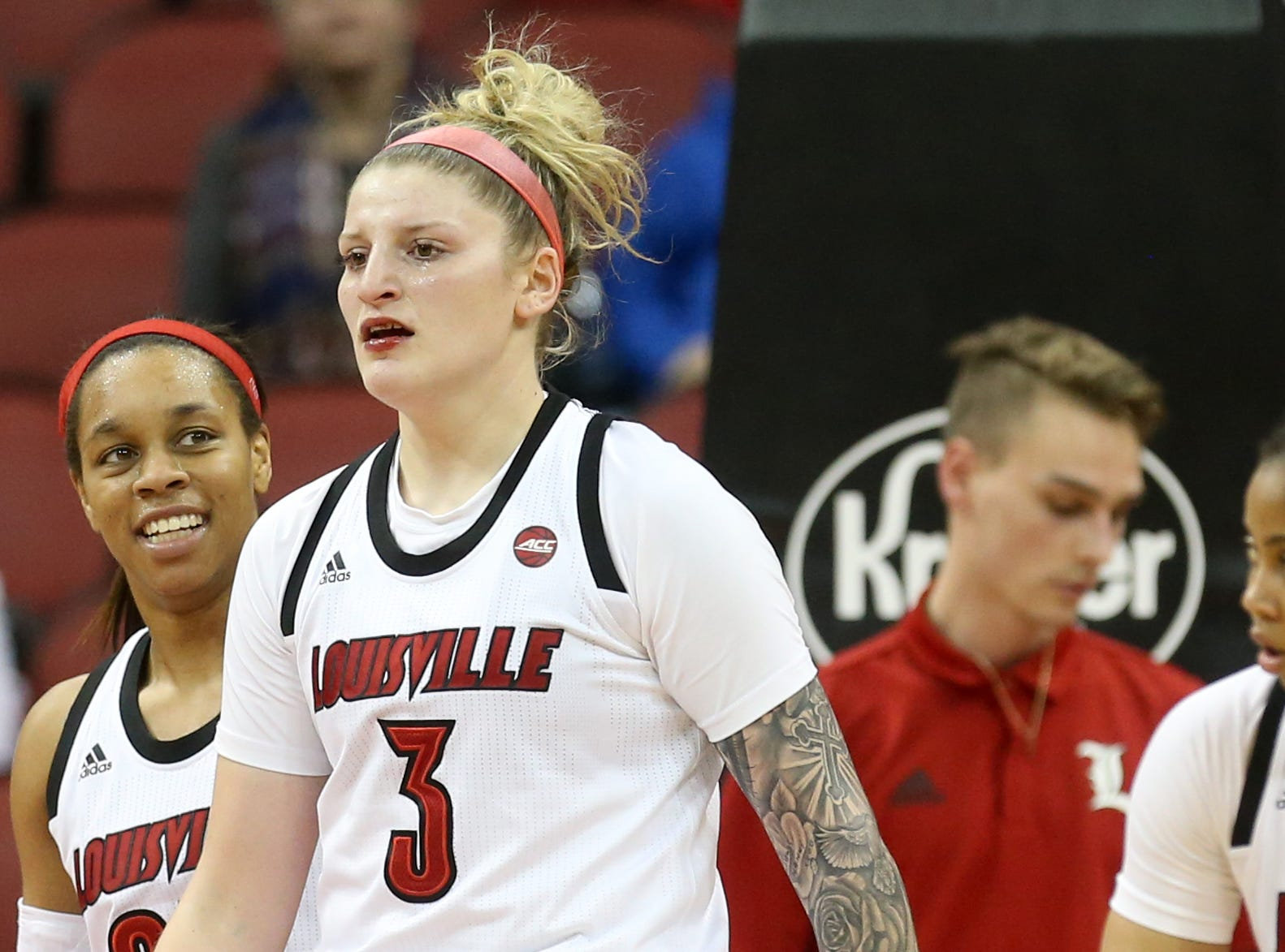 Louisville's Sam Fuerhring heads back to the bench with a bloody lip.