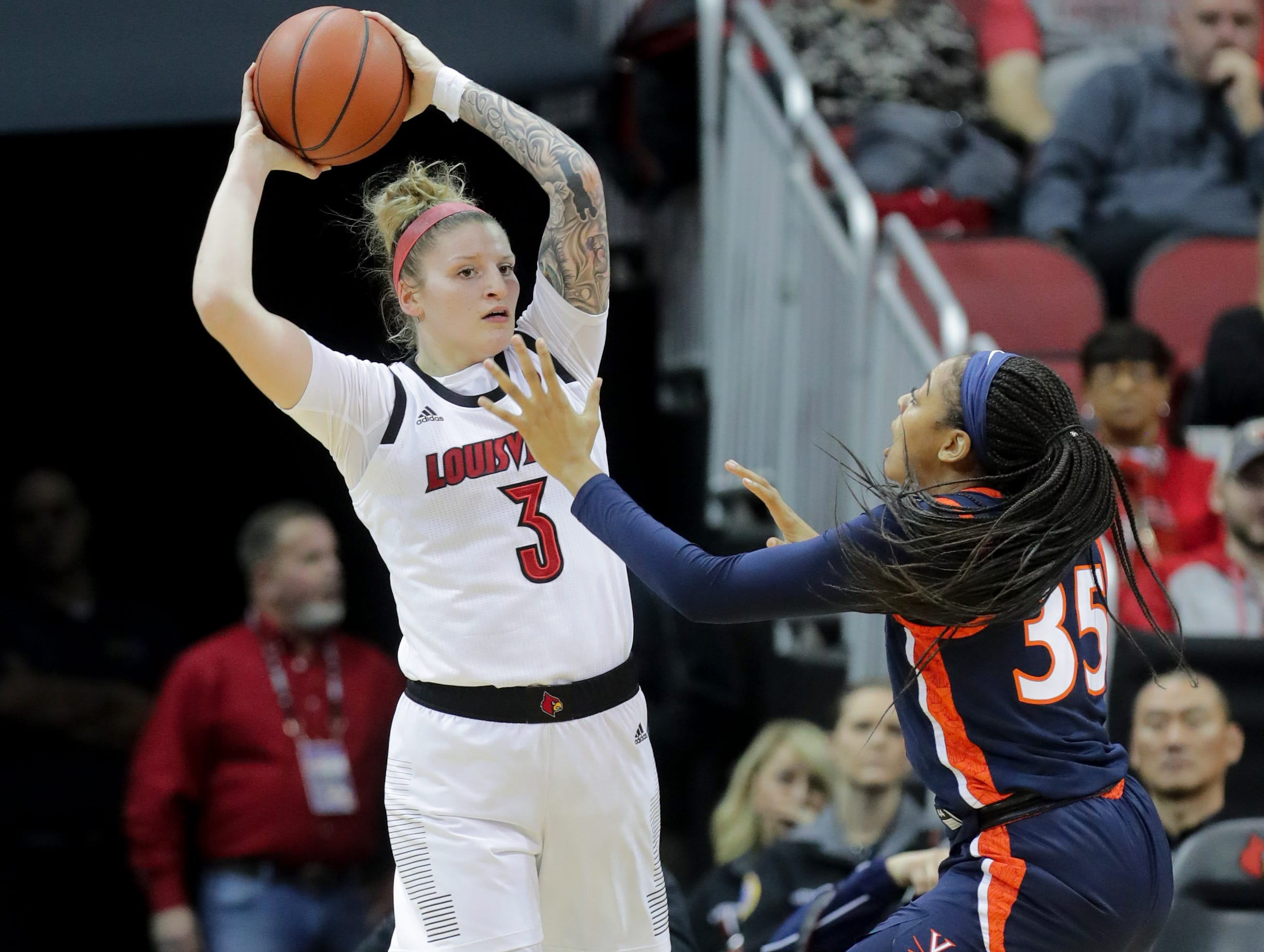 Louisville's Sam Fuerhring is guarded by Virginia's Shakyna Payne.