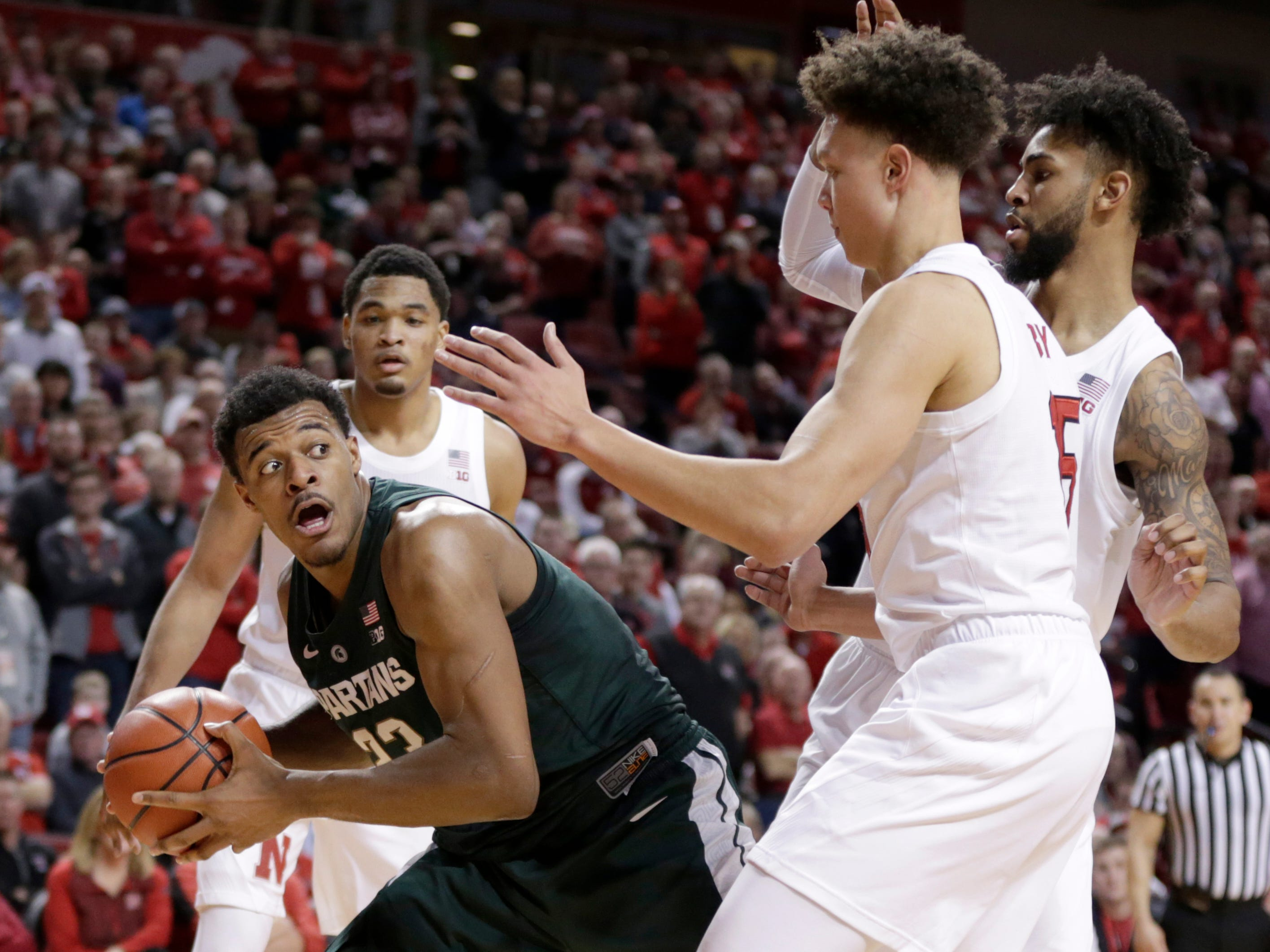 Michigan State's Xavier Tillman (23) looks to pass the ball against Nebraska's James Palmer Jr., left rear, Isaac Copeland Jr., right rear, and Isaiah Roby, right, during the second half of an NCAA college basketball game in Lincoln, Neb., Thursday, Jan. 17, 2019. Michigan State won 70-64.