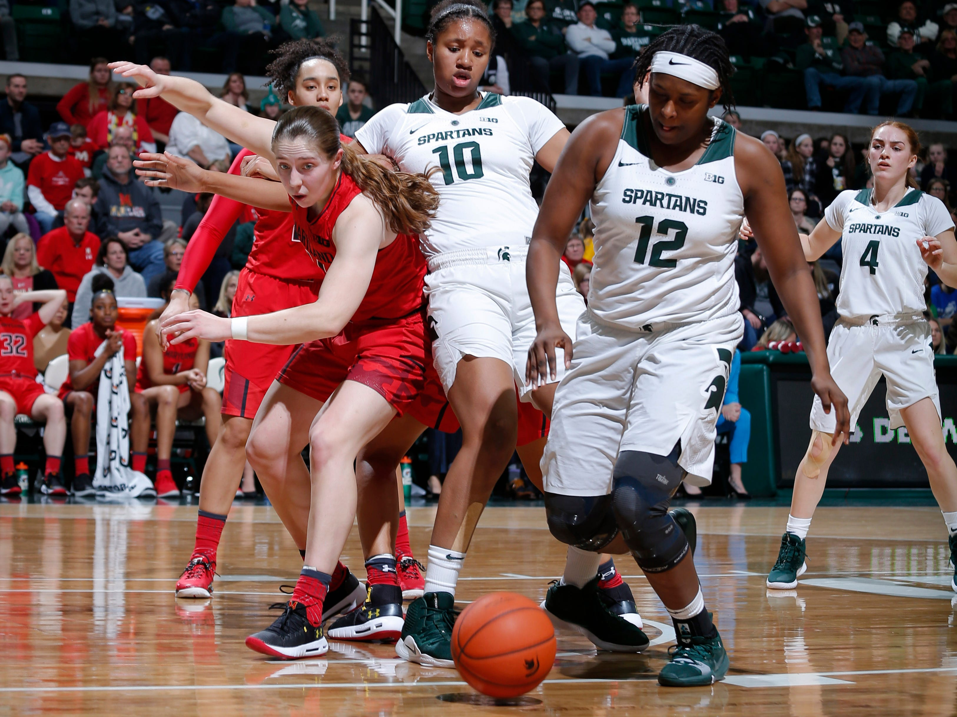 Michigan State's Nia Hollie (12) and Sidney Cooks (10) and Maryland's Taylor Mikesell chase the ball, Thursday, Jan. 17, 2019, in East Lansing, Mich.