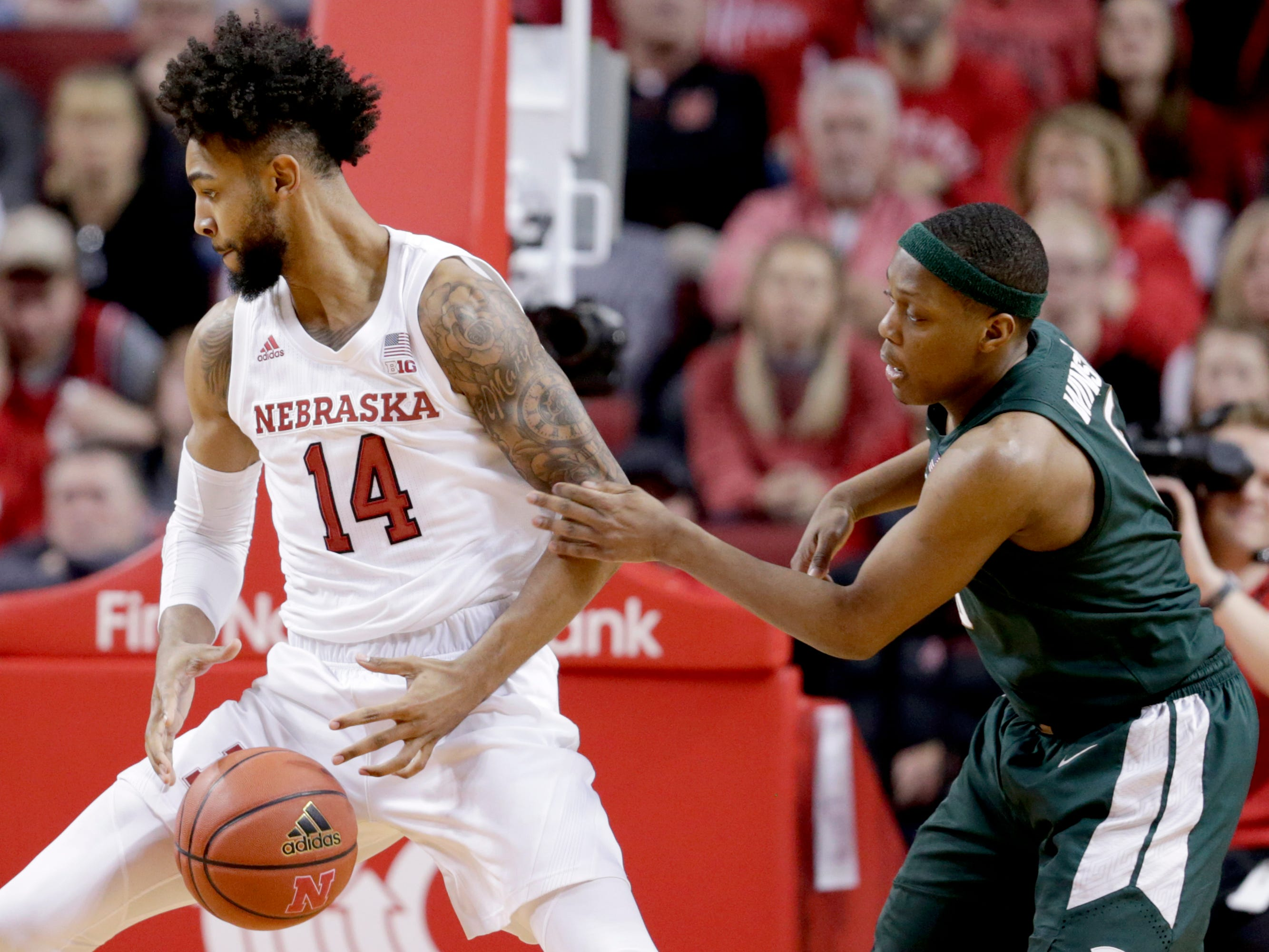Michigan State's Cassius Winston (5) fouls Nebraska's Isaac Copeland Jr. (14) during the second half of an NCAA college basketball game in Lincoln, Neb., Thursday, Jan. 17, 2019. Michigan State won 70-64.
