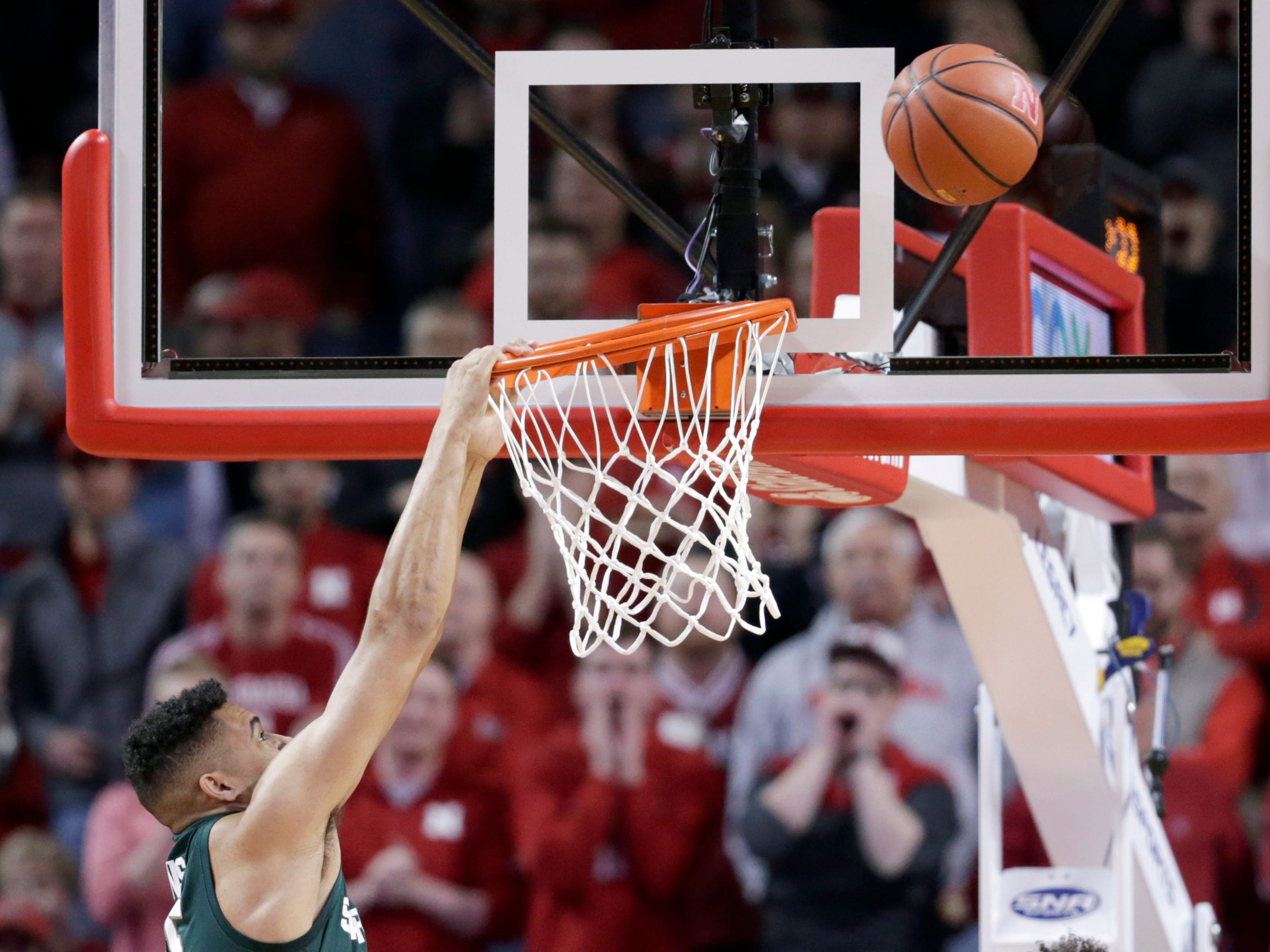Michigan State's Kenny Goins hangs on the rim after missing a dunk during the first half of an NCAA college basketball game against Nebraska in Lincoln, Neb., Thursday, Jan. 17, 2019.