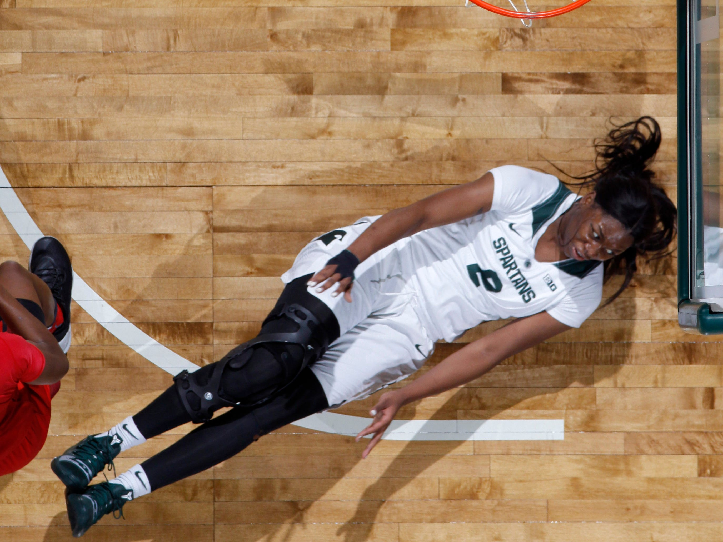 Michigan State's Mardrekia Cook, right, hits the floor after being bulldozed by Maryland's Kaila Charles, left, Thursday, Jan. 17, 2019, in East Lansing, Mich.
