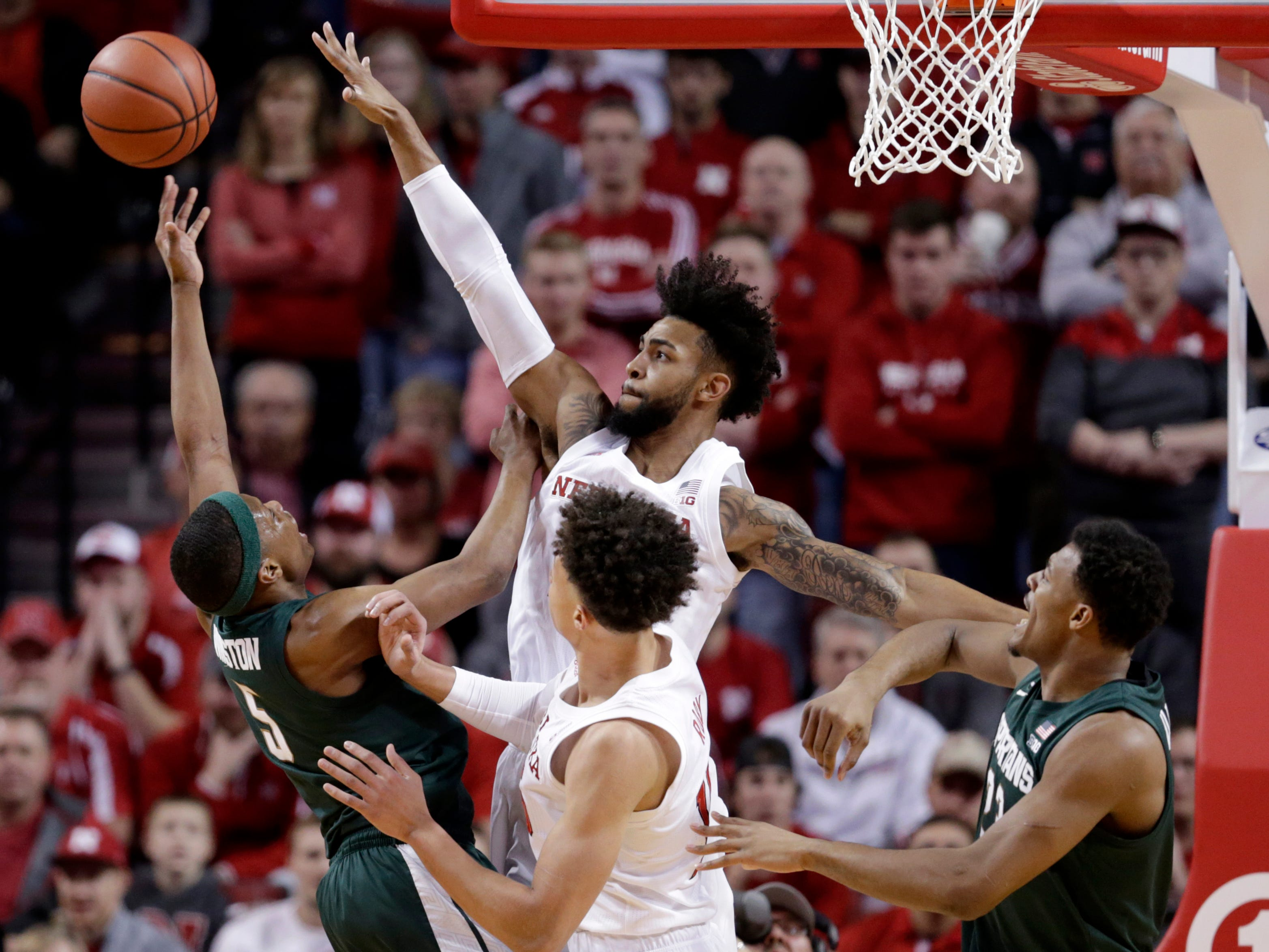 Nebraska's Isaac Copeland Jr., center rear, tries to block a shot by Michigan State's Cassius Winston (5), as Xavier Tillman, right, and Isaiah Roby, center front, watch, during the first half of an NCAA college basketball game in Lincoln, Neb., Thursday, Jan. 17, 2019.