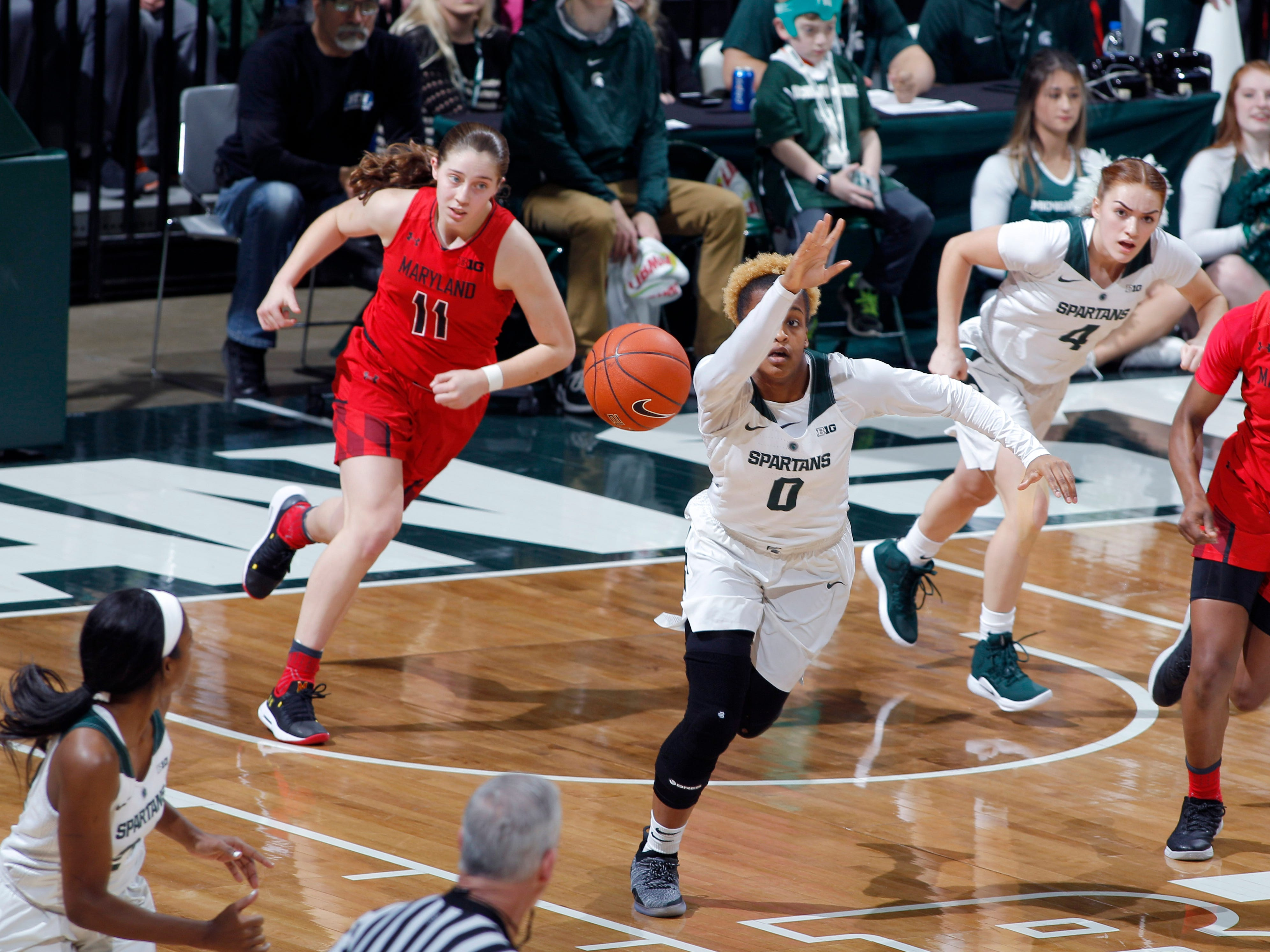 Michigan State's Shay Colley (0) passes to Nia Clouden, left, as they begin a fast break against Maryland, Thursday, Jan. 17, 2019, in East Lansing, Mich.