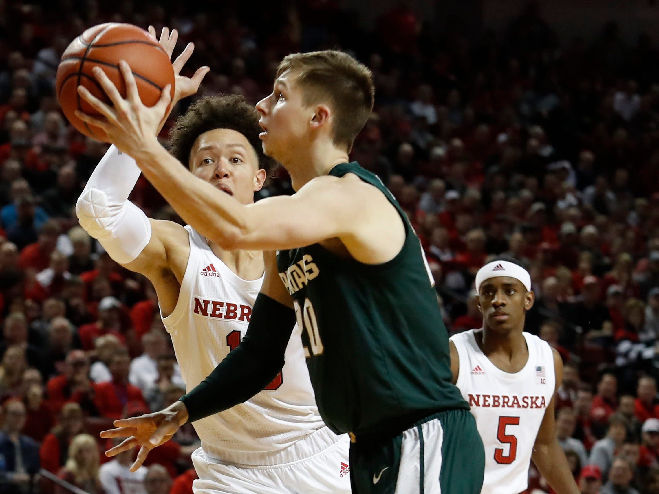 Michigan State Spartans guard Matt McQuaid (20) shoots the ball as Nebraska Cornhuskers forward Isaiah Roby (15) defends in the second half at Pinnacle Bank Arena. Michigan State won 70-64.
