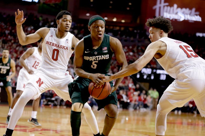 Michigan State's Cassius Winston (5) drives between Nebraska's James Palmer Jr. (0) and Isaiah Roby (15) during the second half of an NCAA college basketball game in Lincoln, Neb., Thursday, Jan. 17, 2019. Michigan State won 70-64.