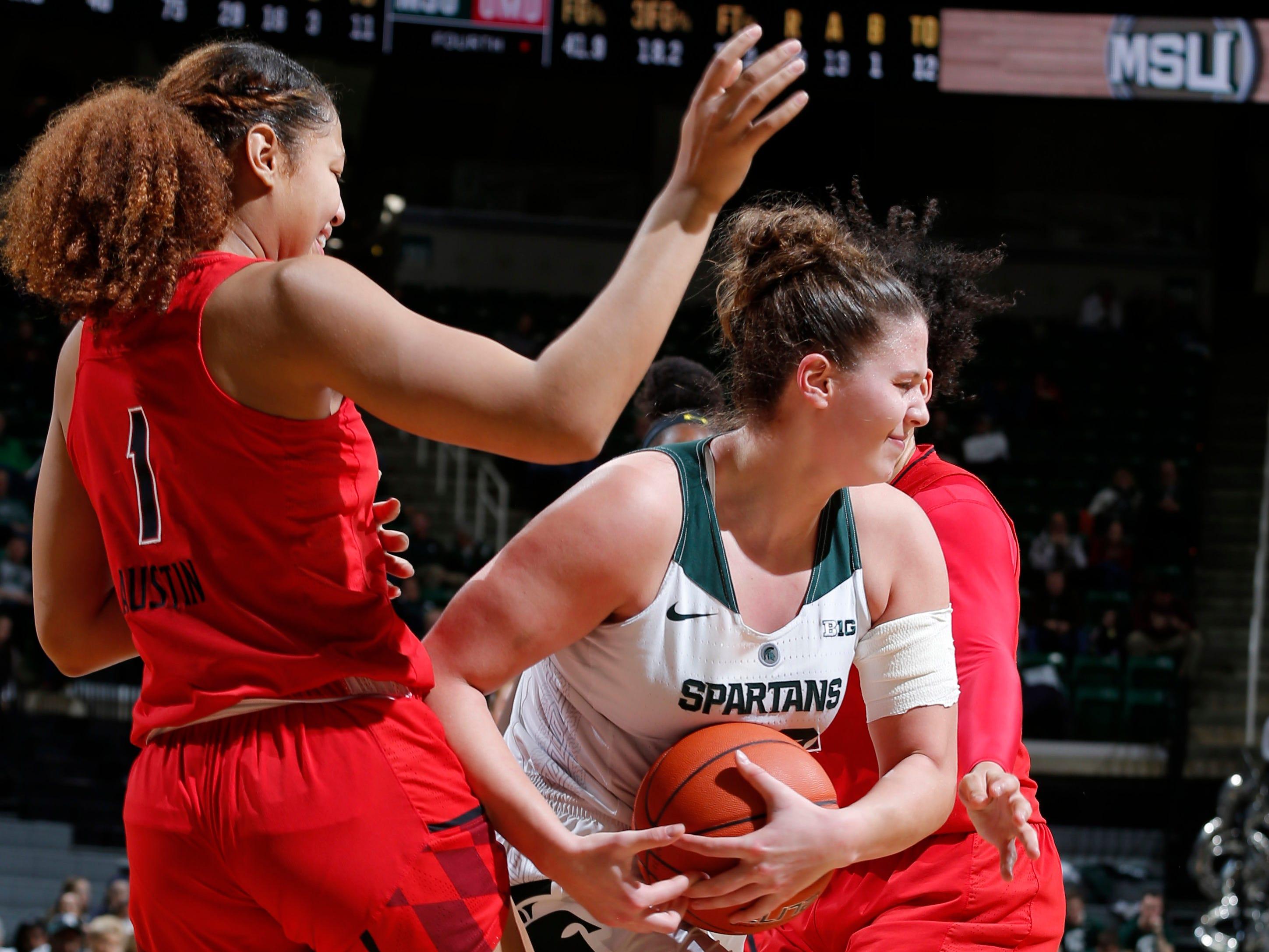 Michigan State's Jenna Allen, center, controls a rebound against Maryland's Shakira Austin, left, Thursday, Jan. 17, 2019, in East Lansing, Mich.