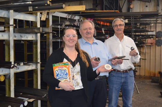 The Epic CNC Training Academy team that includes director Melinda Keway, founder Mike Parker (center) and instructor Mark Dyer display some of the parts they manufacture at their Fenton facility for more than 200 customers' products in 29 states and 12 countries.