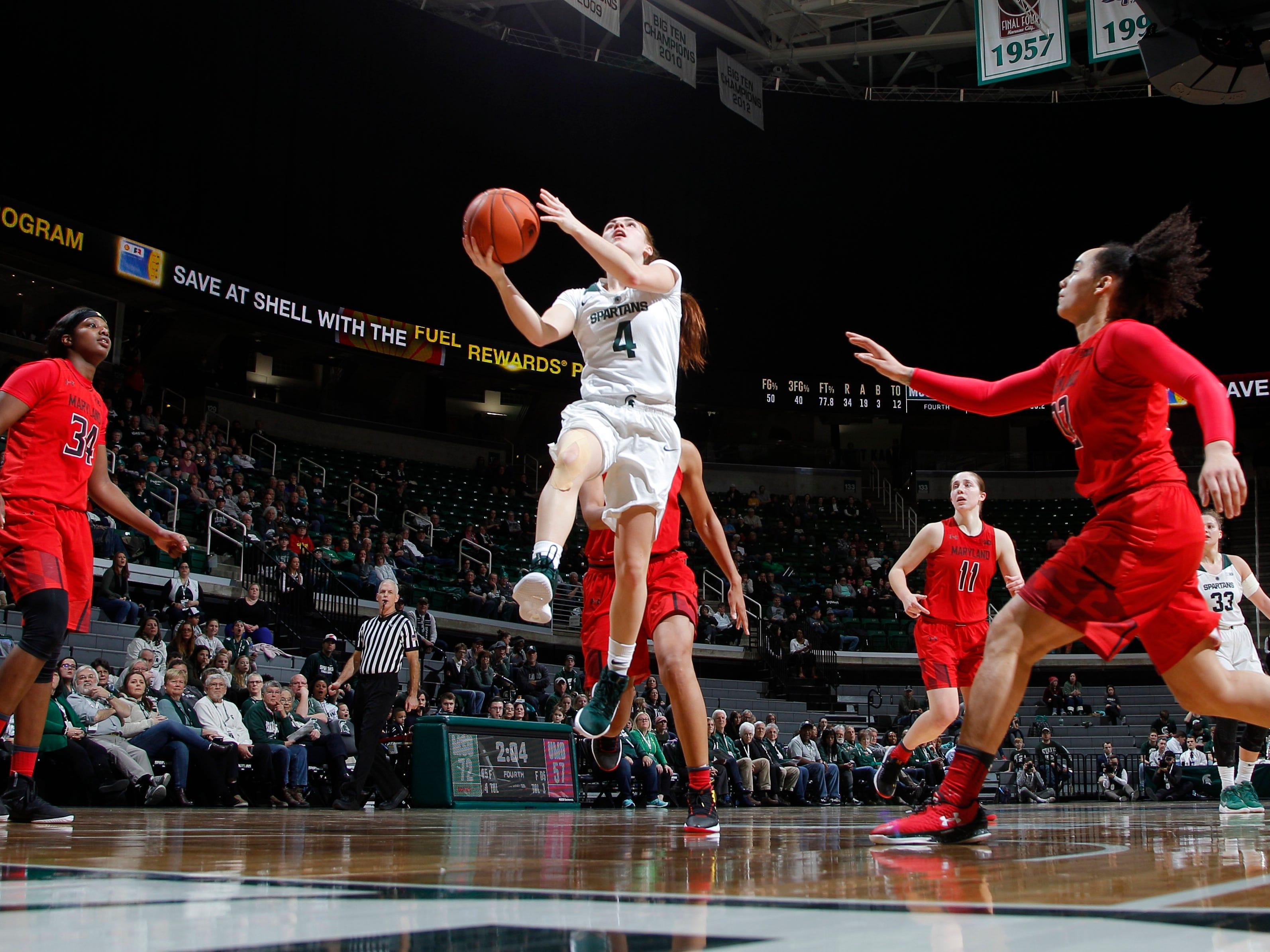 Michigan State's Taryn McCutcheon (4) goes up for a layup against Maryland's Brianna Fraser, left, and Blair Watson, right, Thursday, Jan. 17, 2019, in East Lansing, Mich.