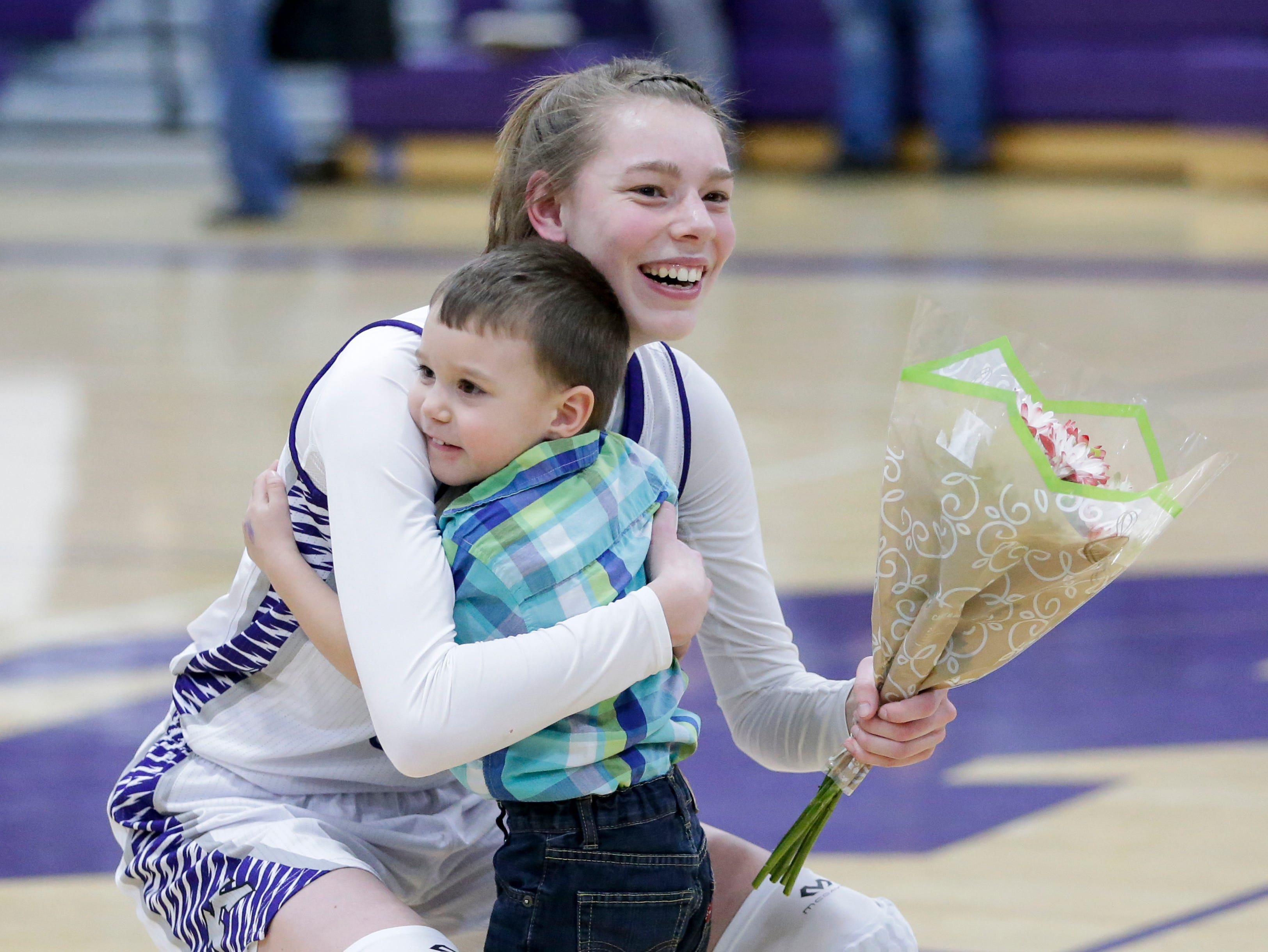 Kiel's Savannah Walsdorf (14) gets a hug from her coach's son Jaxon Bushman as she is recognized for being the Raiders' first girl basketball player to join the 1,000 point club before an EWC matchup against Roncalli at Kiel High School Thursday, January 17, 2019, in Kiel, Wis. Joshua Clark/USA TODAY NETWORK-Wisconsin