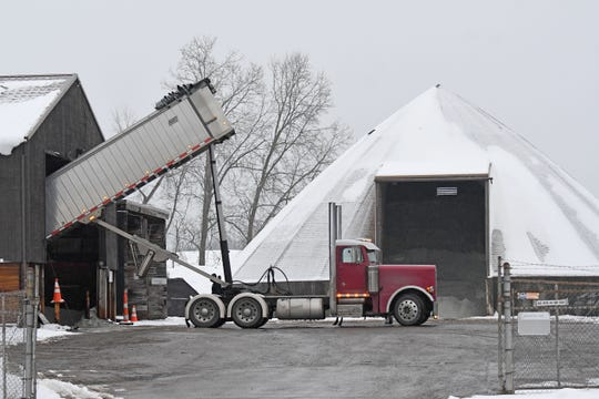 A truck delivering road salt from Sandusky, Ohio is unloaded at the ODOT garage on Fourth Street in Mansfield early Friday morning as preparations are underway for the weekend's winter weather.
