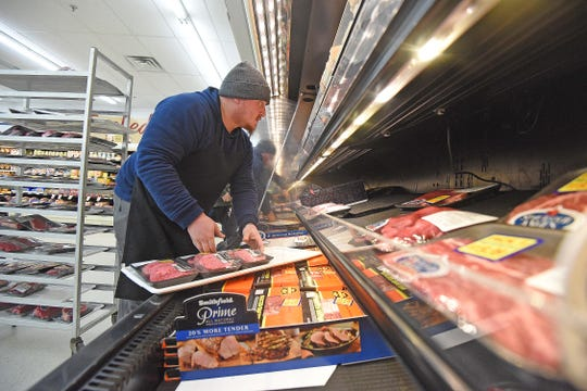 Cody Hamilton works hard to keep up with the demand for meat at Main Street Market in Lexington on Friday afternoon as customers stock up early before the storm predicted for this weekend.