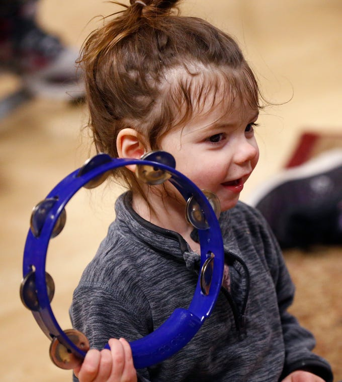 Carolie King, 3, plays a tambourine during a free parent and child music class on Jan. 17 offered by Nick Meske as a promotion for a six-week class he will be offering through the Oconomowoc Recreation Department at the Community Center.