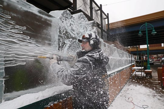 Aaron Costic works on the sculptures and ice wall in front of the St. Paul Fish Co at the Milwaukee Public Market. Ice bars opened in the Third Ward Jan. 18. The ice sculptures were done by Art Below Zero.
