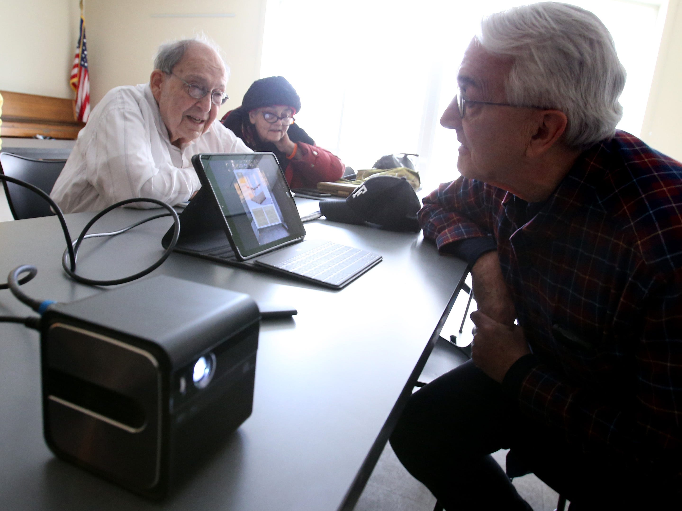 Peter Lee demonstates to Len Levine and Katie Briggs a recently released GoSho portable high-definition projector that can connect to touch devices and computers during a gathering of If It Goes Beep, an informal discussion and problem solving group that meets at 9 a.m. Fridays at the Shorewood Senior Resource Center. The Center also offers One-to-One Tech Support Fridays from 9 a.m. to 11:30 a.m. for people to stop in with their technology questions.