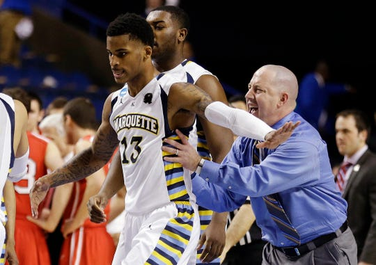 Marquette guard Vander Blue (13) and head coach Buzz Williams celebrate after Blue hit the winning basket against Davidson with one second left in their second-round NCAA college basketball tournament game, Thursday, March 21, 2013, in Lexington, Ky. Marquette won 59-58.