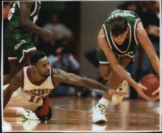 Wisconsin guard Darnell Hoskins reaches as University of Wisconsin- Green Bay's Jeff Nordgaard scoops up the ball in 1994.