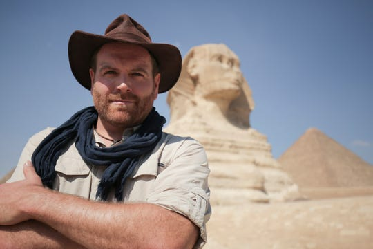 "Josh Gates poses in front of the Great Sphinx in Egypt on his Travel Channel series ""Expedition Unknown."" Friday, he'll be onstage at the Marcus Center."