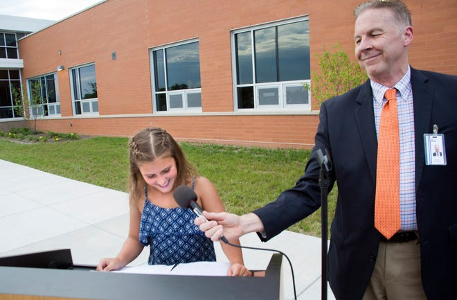 Forest Ridge Elementary School fourth-grader Elly Posig speaks during the school's grand opening ceremony Aug. 29, 2016, as superintendent Tim Culver holds the microphone. Culver will be stepping down as Oak Creek-Franklin superintendent in August.