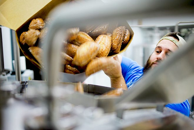 Joey Carioti, co-owner of Cranky Al's in Wauwatosa, pours his signature crullers in a batch of beer at Vennture Brew Co.,5519 W. North Ave. The beer will be unveiled Jan. 26.