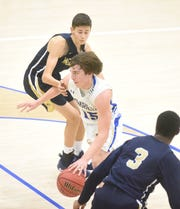 Mountain Home's Colton Peters drives between two defenders during a recent home game.