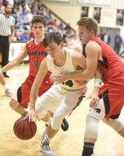Izard County's Dalton Dillard drives between Norfork's Bryson Thiel (3) and Kyle Crawford on Thursday night.