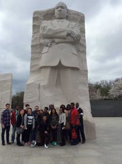 A group of MPS students  gather in Washington D.C. in front of a statue of Martin Luther King Jr. They were participants in the Marching On program.