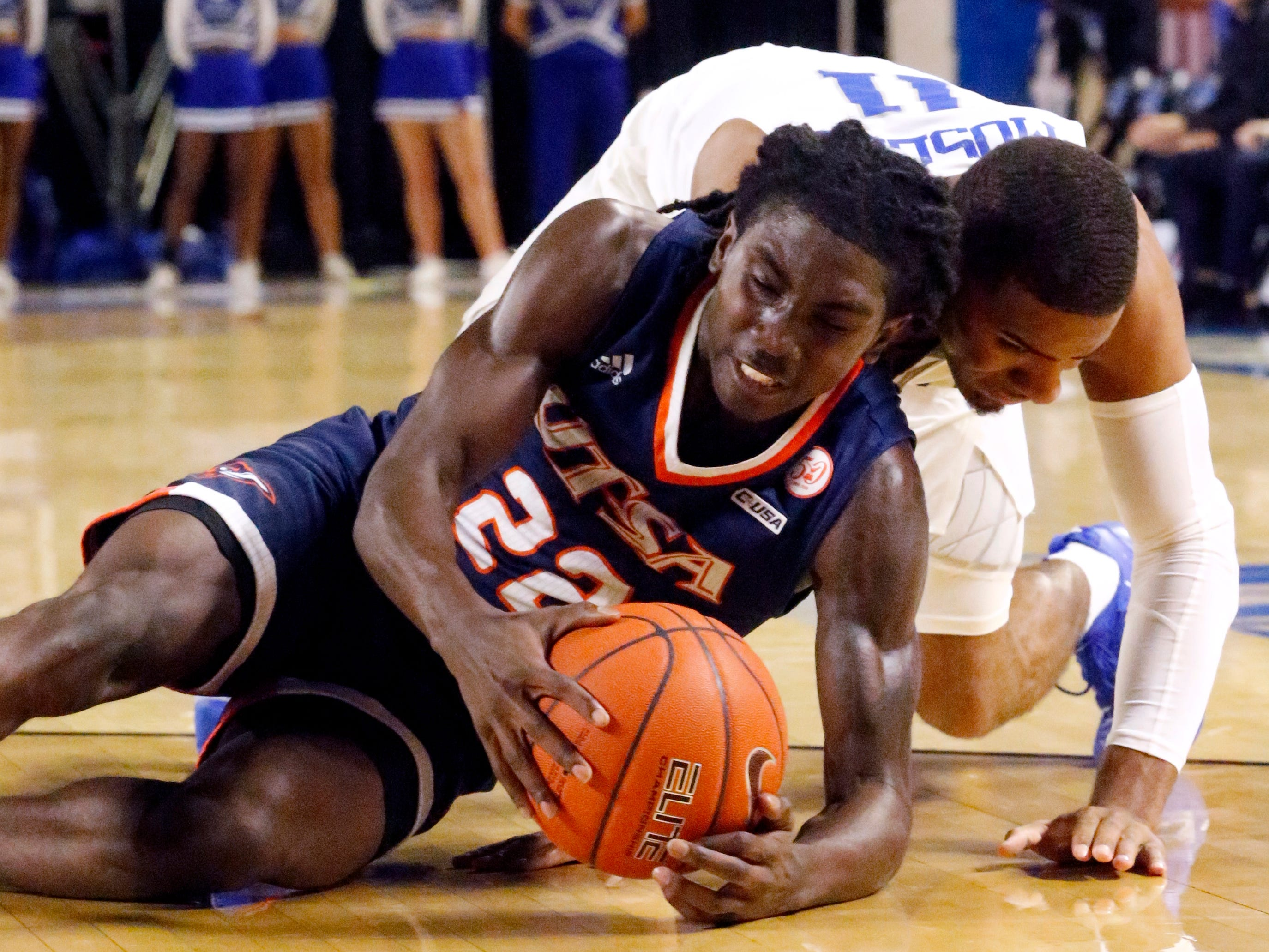 MTSU's guard Lawrence Mosley (11) falls with the ball as UTSA's forward Austin Timperman (32) grabs the loose ball on Thursday Jan. 17, 2019.