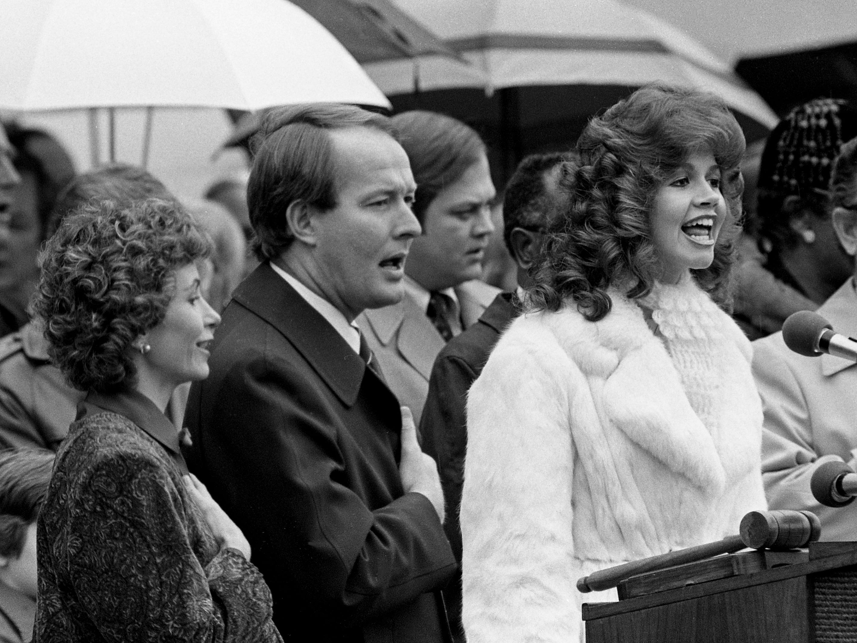 Lynn Golden, right, a student of Lee College in Cleveland, Tenn., sings the national anthem with Honey and Gov. Lamar Alexander joining in during the inauguration ceremonies for Alexander at the Legislative Plaza on Jan. 20, 1979.