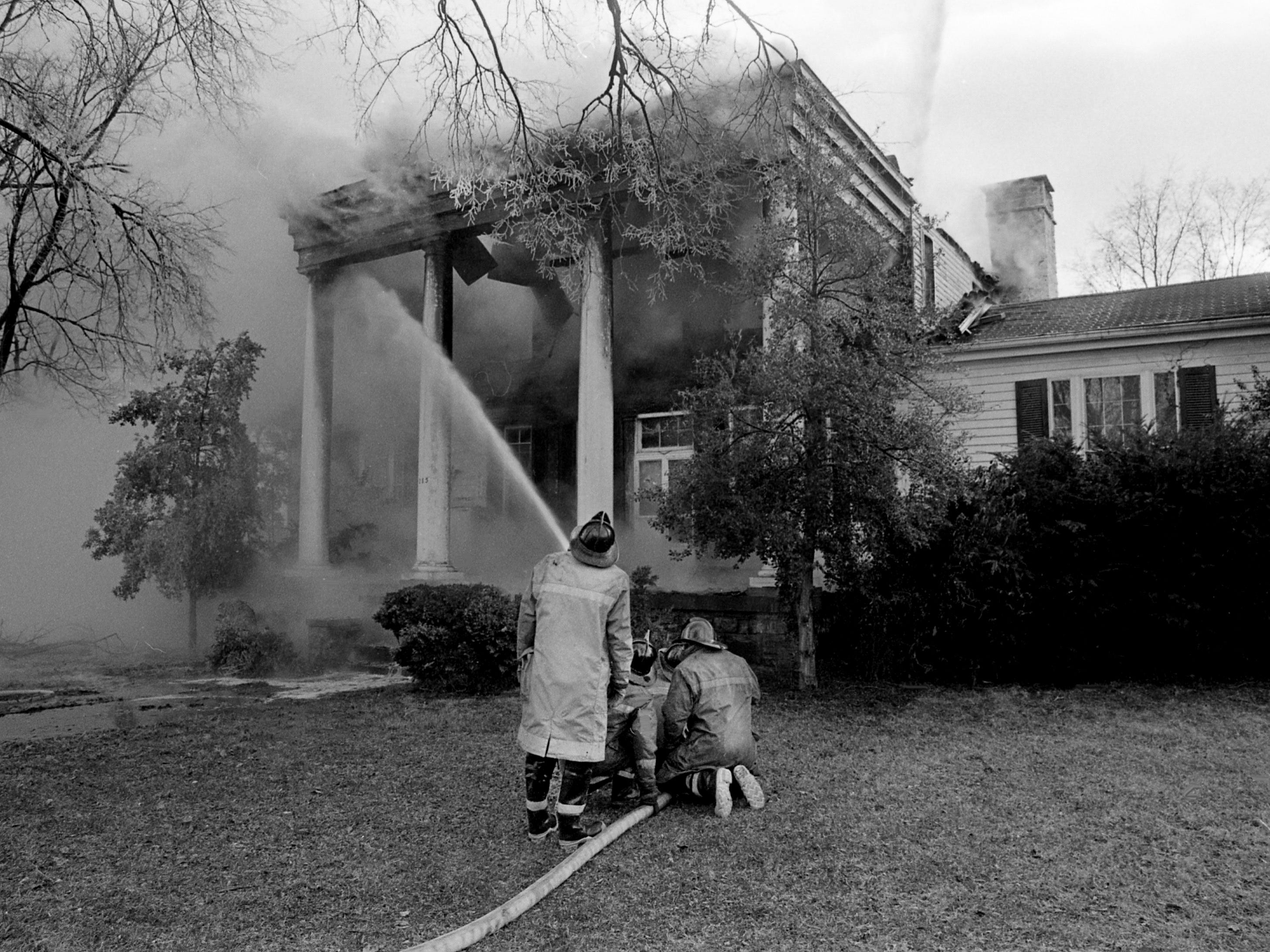 Firefighters pour water into a blaze that heavily damaged the upper floors of a vacant house at 215 Blanton Ave. on Jan. 2, 1979. The house was built in 1804 by G.M. Hill, father of the late Nashville business leader H.G. Hill.