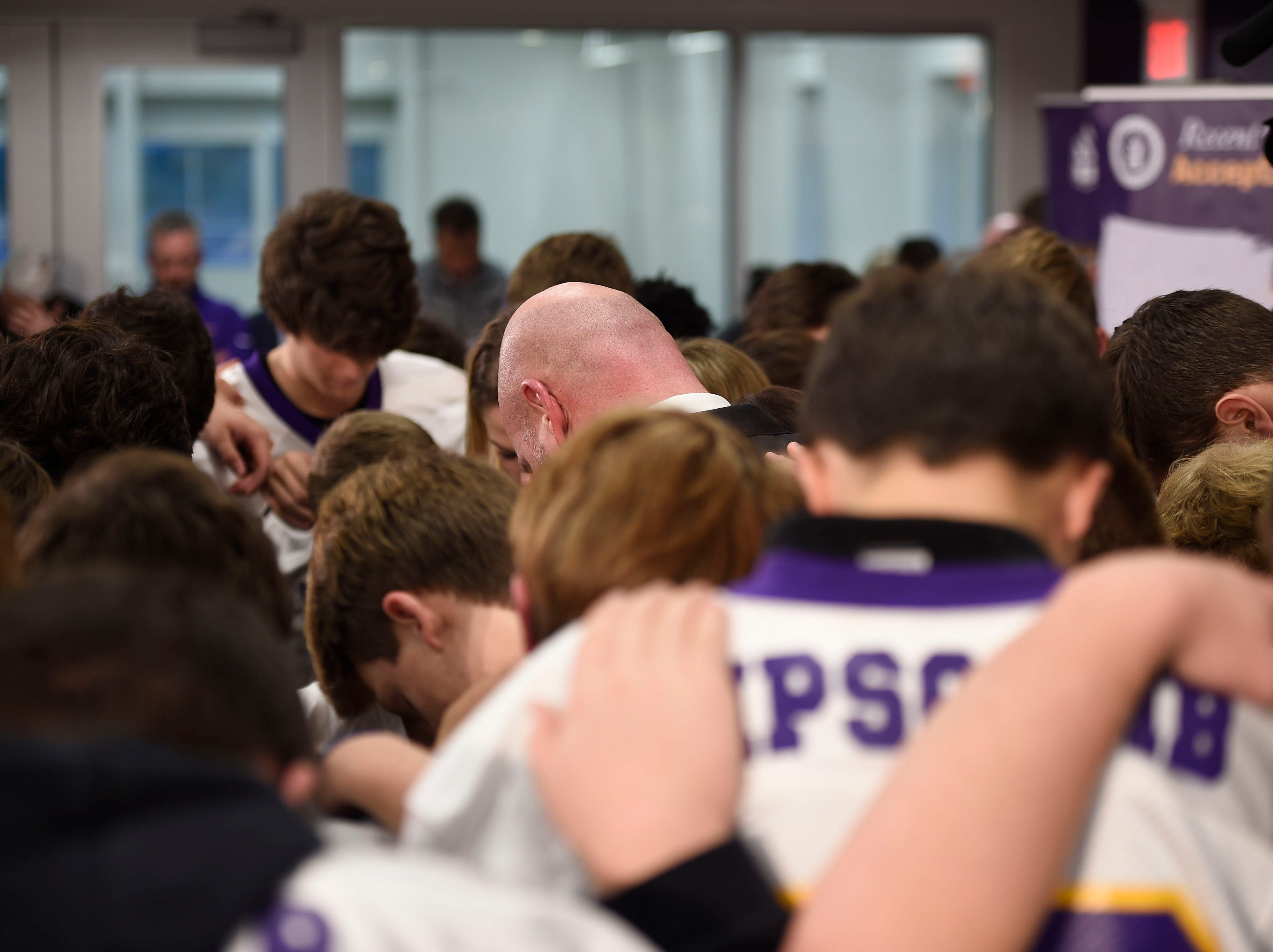 The Lipscomb Academy football team surrounds new head coach Trent Dilfer and his family for a post press conference prayer.