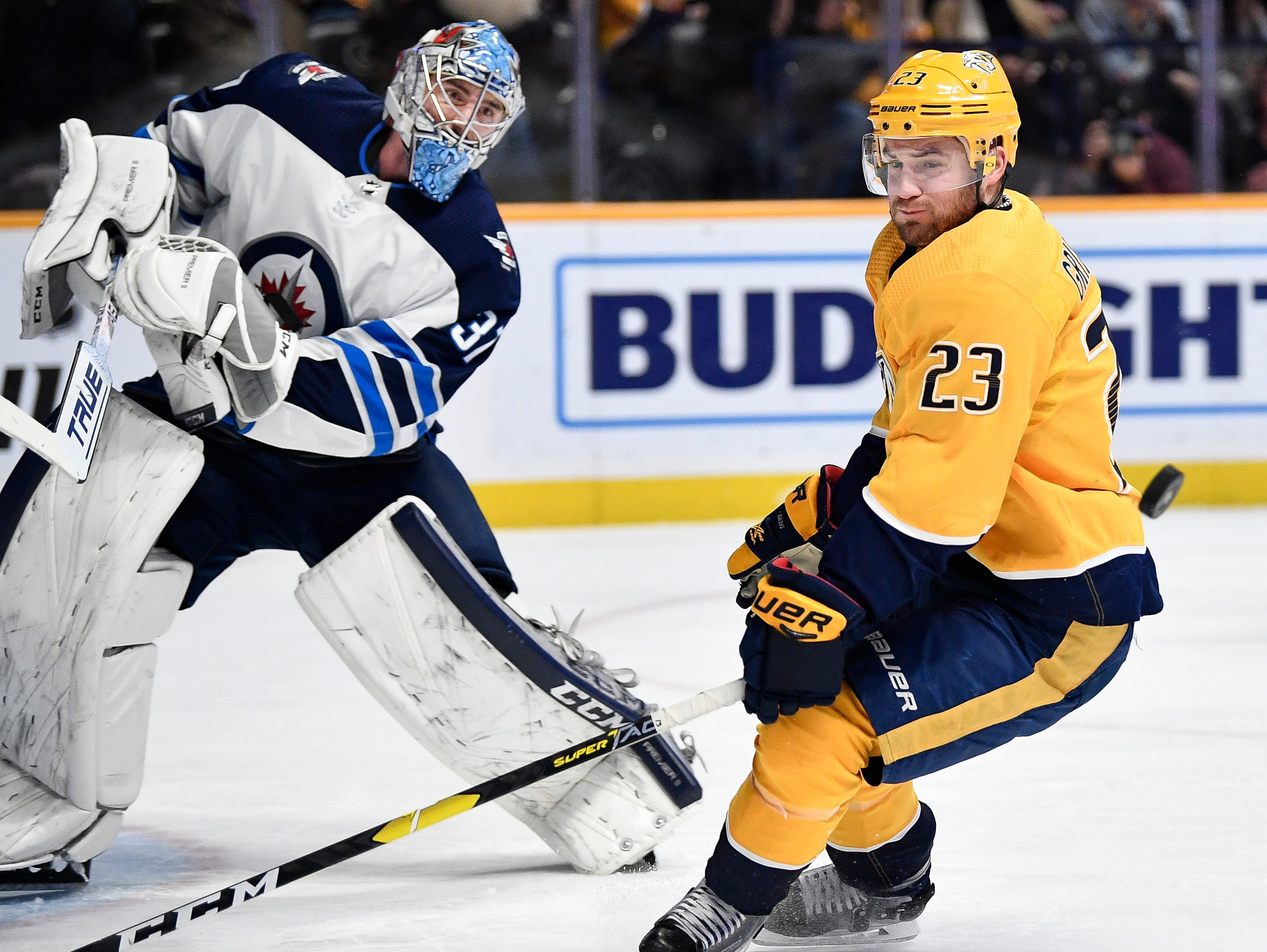Winnipeg Jets goaltender Connor Hellebuyck (37) bats a shot away from Nashville Predators center Rocco Grimaldi (23) during the first period at Bridgestone Arena in Nashville, Tenn., Thursday, Jan. 17, 2019.