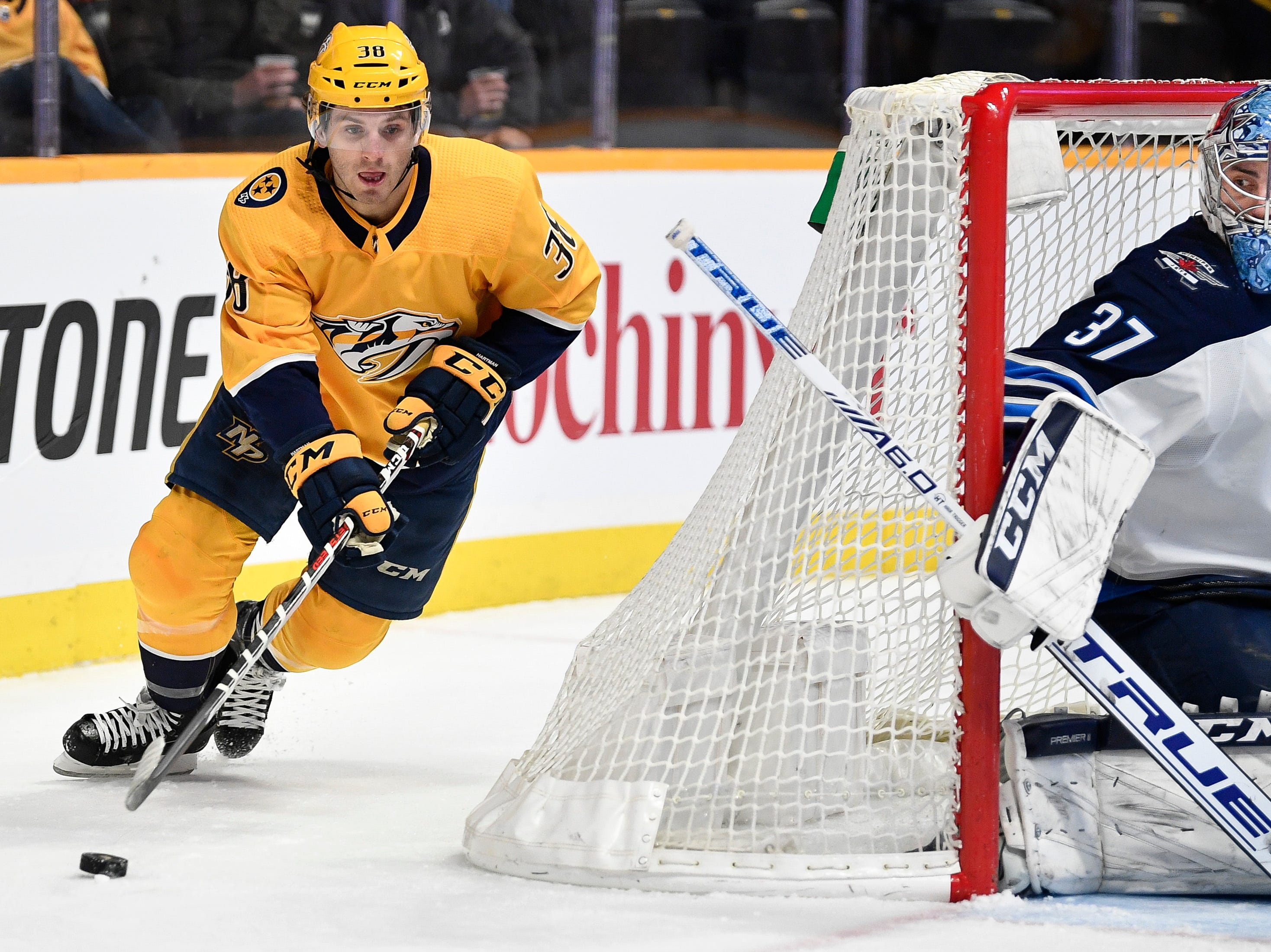 Nashville Predators right wing Ryan Hartman (38) maneuvers past Winnipeg Jets goaltender Connor Hellebuyck (37) during the first period at Bridgestone Arena in Nashville, Tenn., Thursday, Jan. 17, 2019.