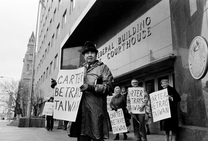 While most folks are sleeping off the effects of New Year's Eve, the Rev. Mel Perry, front, and some members of his congregation gather outside the Federal Courthouse on Jan. 1, 1979, to protest the normalization relations between U.S. and the People's Republic of China.