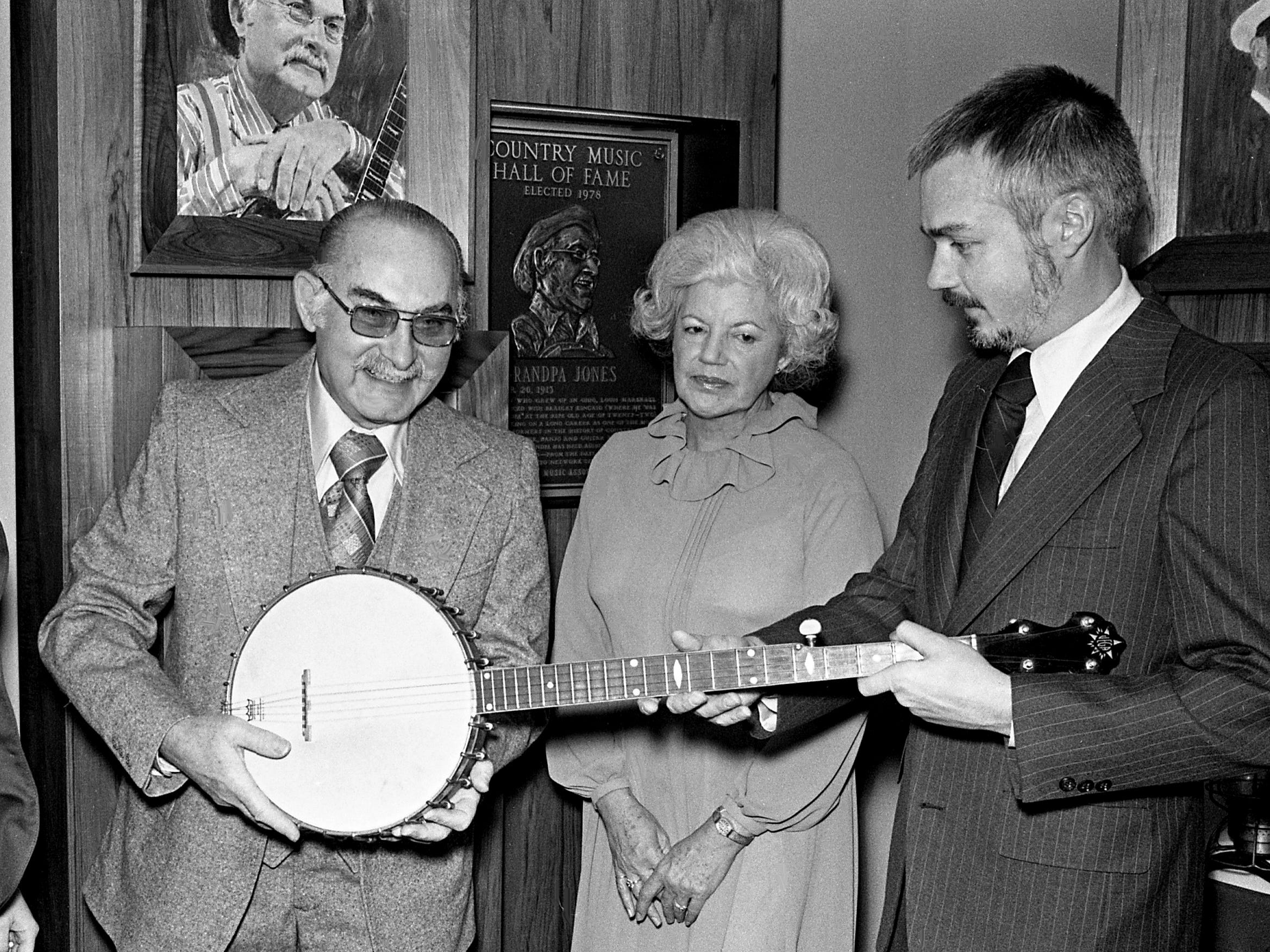 During ceremonies marking his induction in the Country Music Hall of Fame on Jan. 31, 1979, Grandpa Jones, left, took time for a little picking and grinning. Looking on are his wife Ramona and Country Music Foundation Director Bill Ivey.