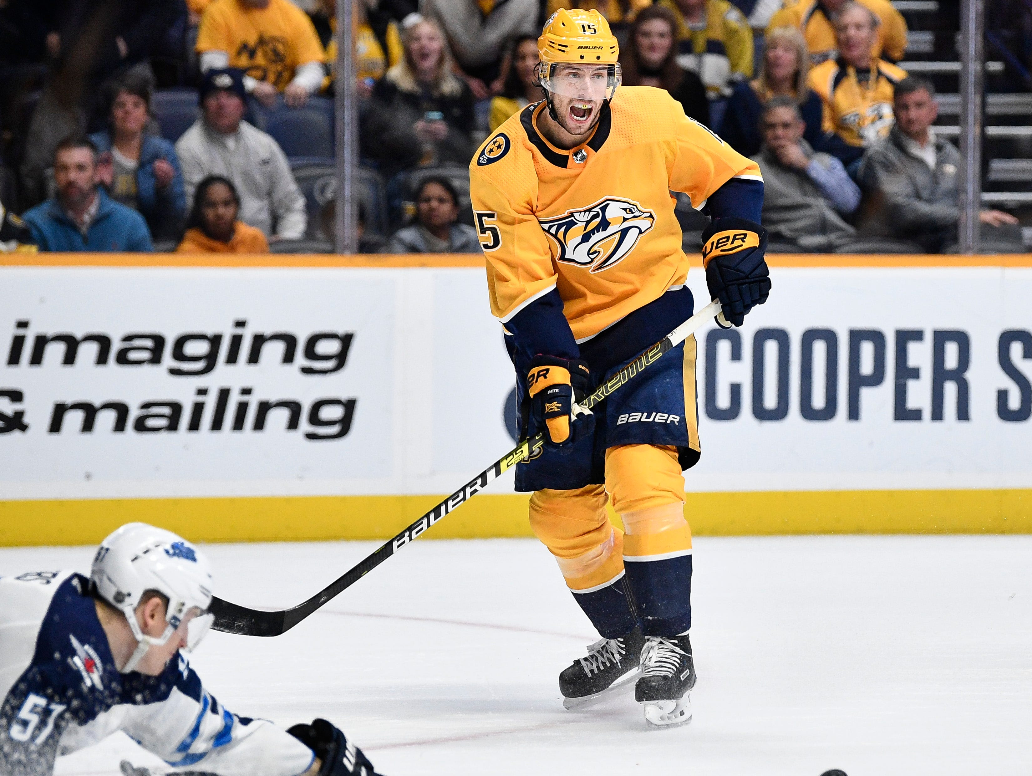 Nashville Predators right wing Craig Smith (15) has a pass deflected by Winnipeg Jets defenseman Tyler Myers (57) during the first period at Bridgestone Arena in Nashville, Tenn., Thursday, Jan. 17, 2019.
