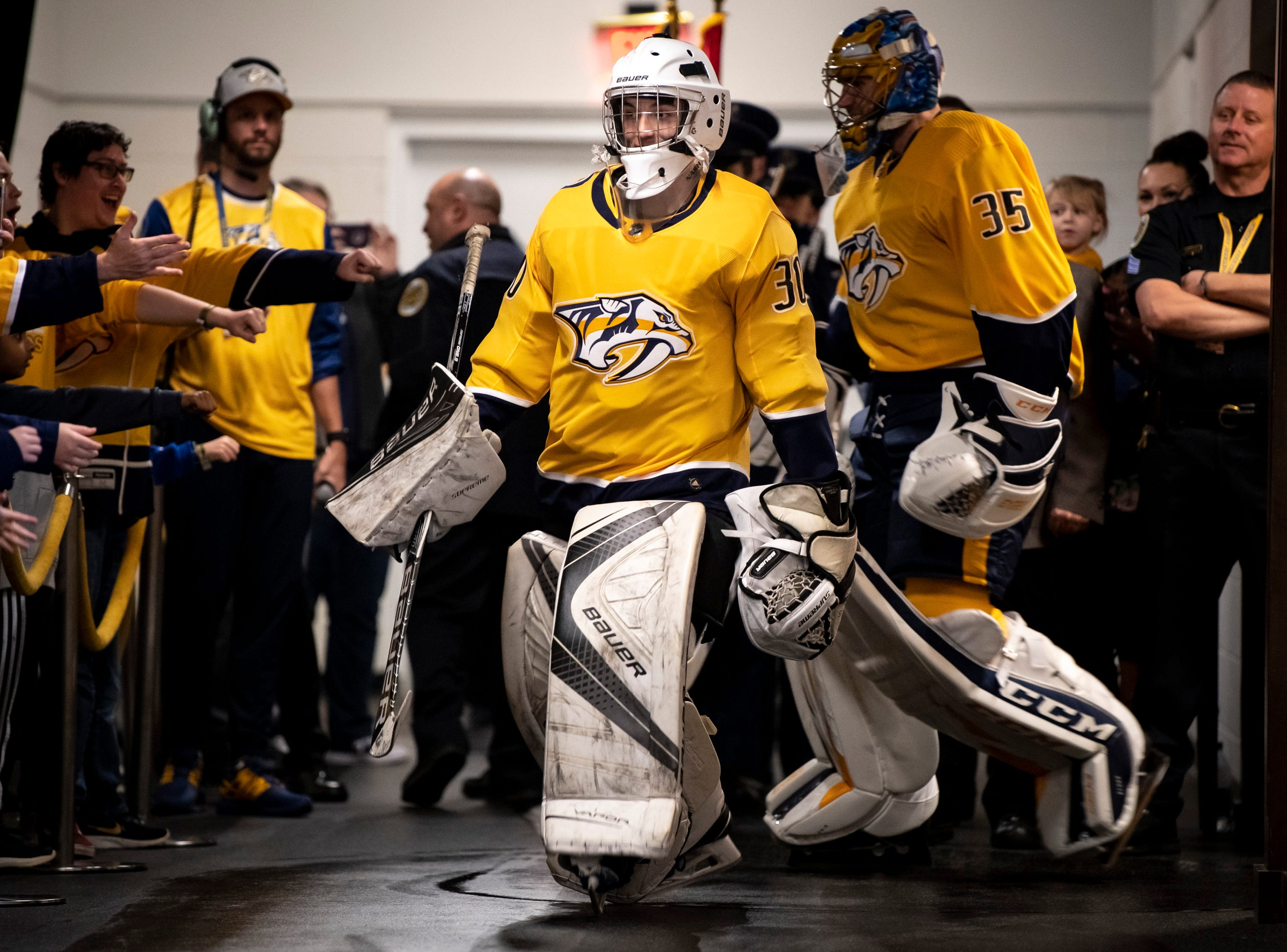 Make-A-Wish recipient and Ionia resident Jacob Piros heads out to the ice wearing a Predators jersey followed by Nashville Predators goaltender Pekka Rinne (35) before a game between the Nashville Predators and the Winnipeg Jets at Bridgestone Arena in Nashville, Tenn., Thursday, Jan. 17, 2019.