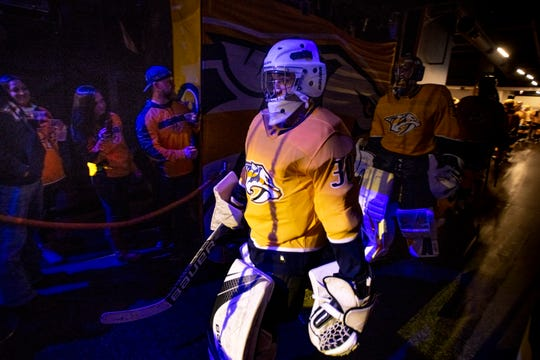 Make-A-Wish recipient Jacob Piros of Ionia heads out to the ice wearing a Predators jersey followed by Nashville Predators goaltender Pekka Rinne (35) before a game between the Nashville Predators and the Winnipeg Jets at Bridgestone Arena in Nashville, Tenn., Thursday, Jan. 17, 2019.