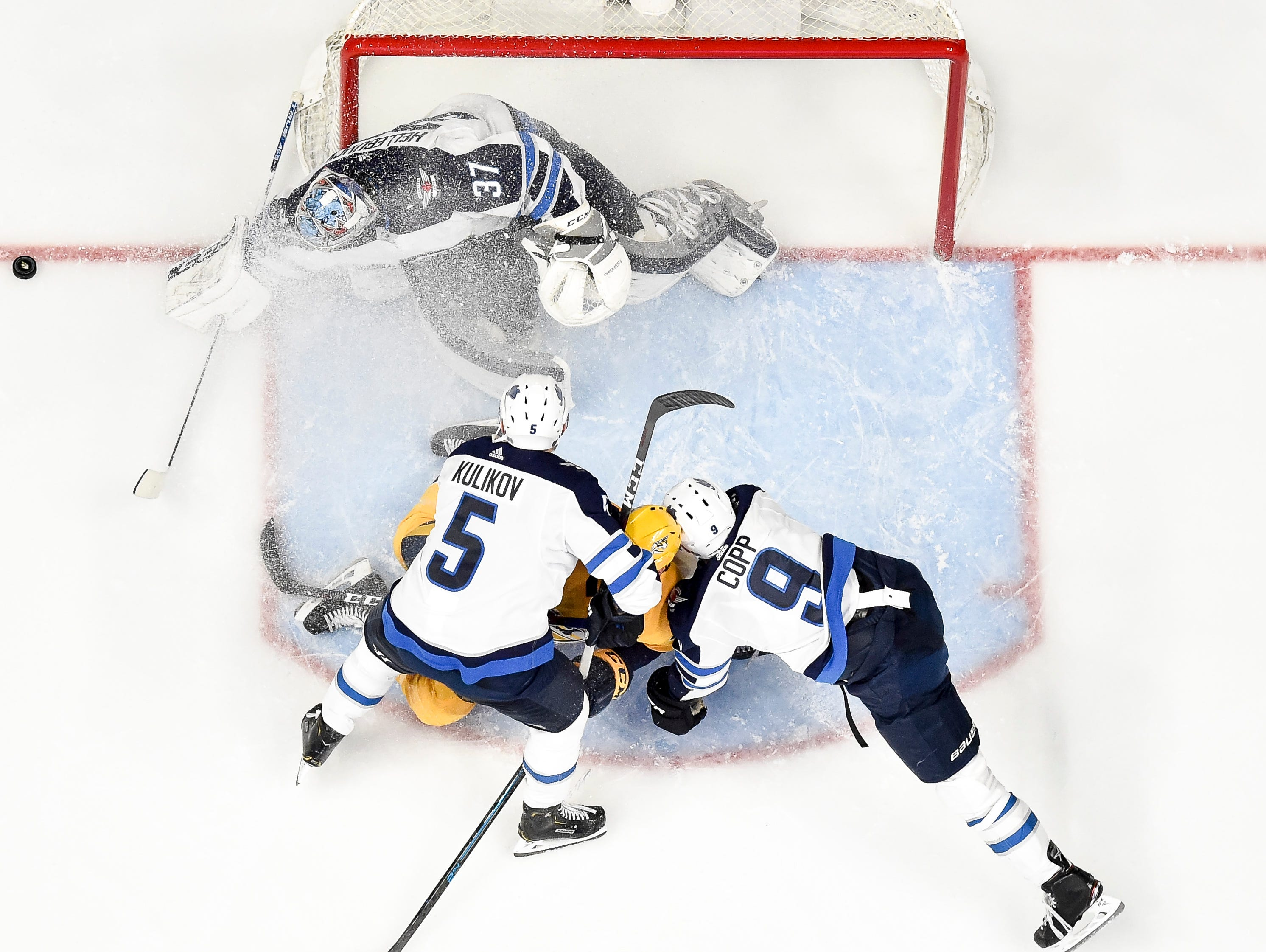 Winnipeg Jets goaltender Connor Hellebuyck (37), defenseman Dmitry Kulikov (5), and center Andrew Copp (9) defend against Nashville Predators center Colton Sissons (10) during the second period at Bridgestone Arena in Nashville, Tenn., Thursday, Jan. 17, 2019.
