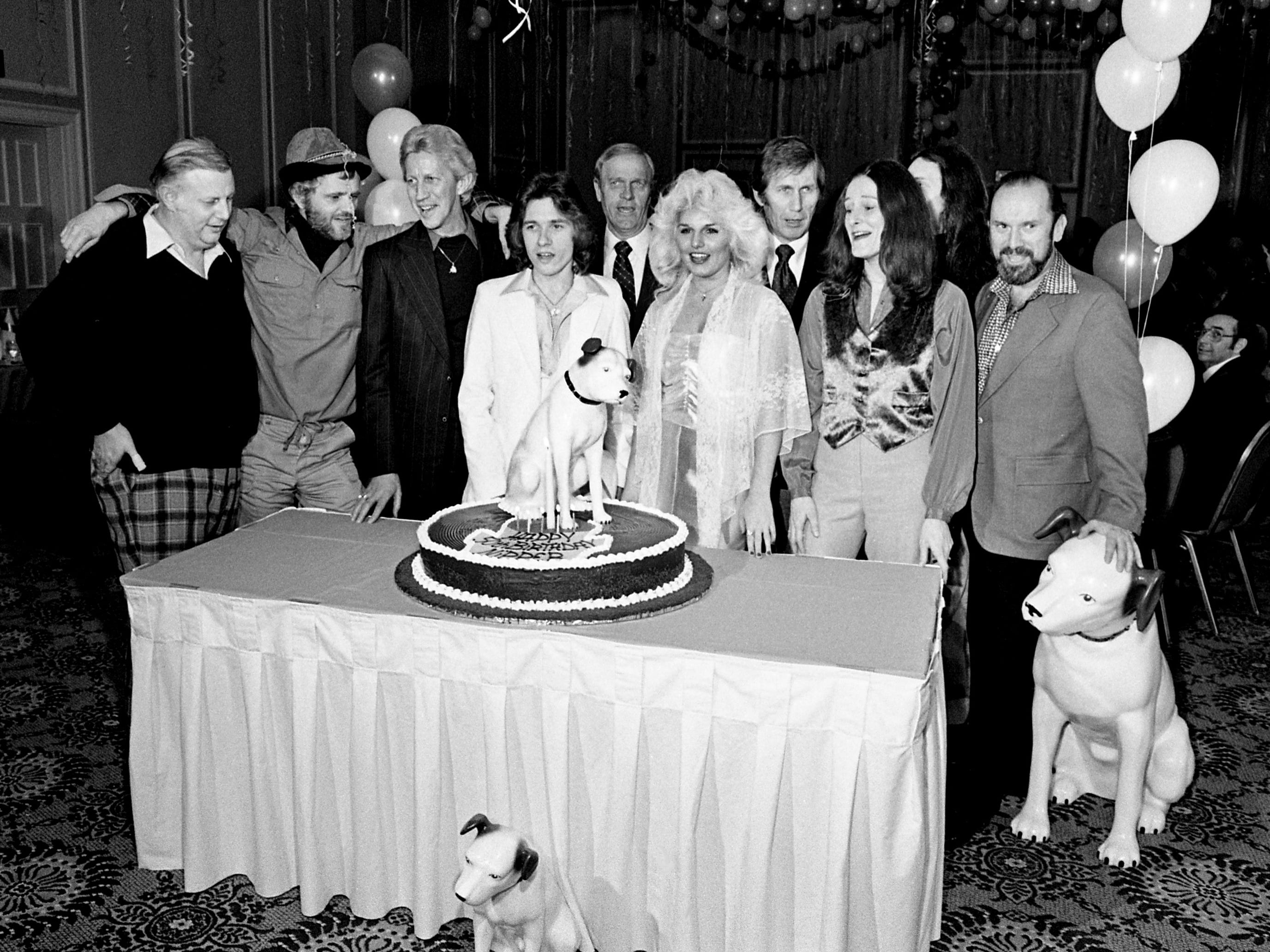 "Some of RCA Records' sales and promotion staff, national executives and recording artists gather around the cake to celebrate RCA's 50th anniversary during a gala dinner at the Opryland Hotel on Jan. 3, 1979. The giant corporation dates its entry into the record business to Jan. 4, 1929, when the Radio Corporation of America first acquired the Victor Talking Machine Company and its famous ""Nipper"" trademark."
