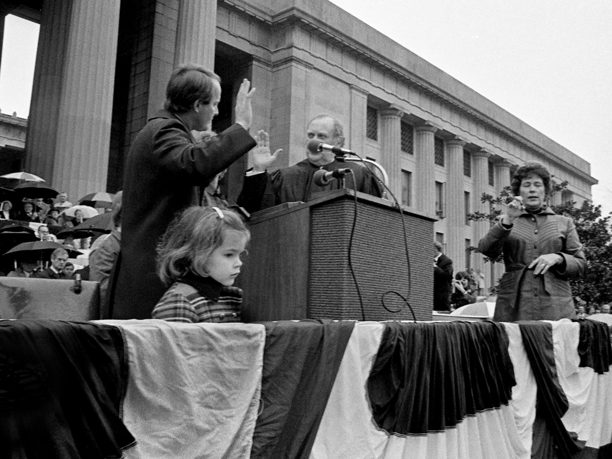 With daughter Kathryn, 4, front left, looks over the packed Legislative Plaza as her dad, Gov. Lamar Alexander, takes the oath of office for the second time in four days from Chief Justice Joe Henry on Jan. 20, 1979.