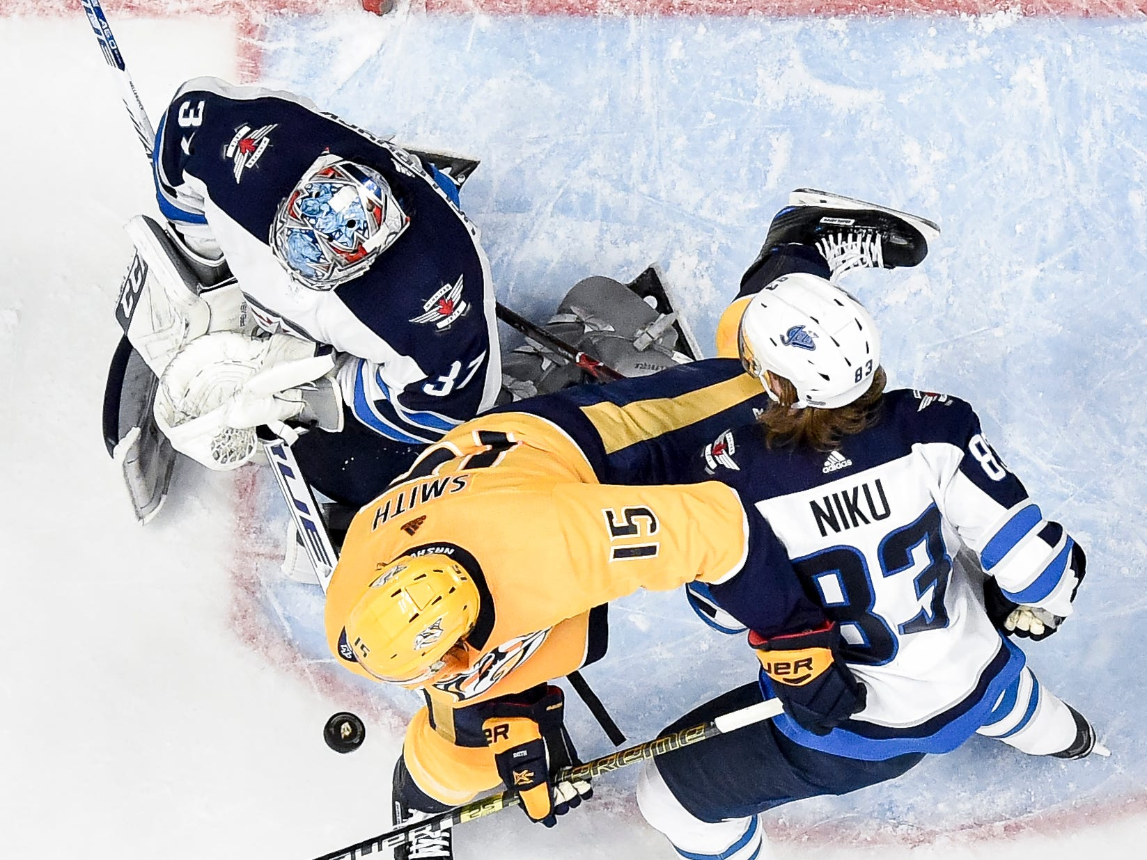 Nashville Predators right wing Craig Smith (15) battles Winnipeg Jets goaltender Connor Hellebuyck (37) and defenseman Sami Niku (83) during the second period at Bridgestone Arena in Nashville, Tenn., Thursday, Jan. 17, 2019.