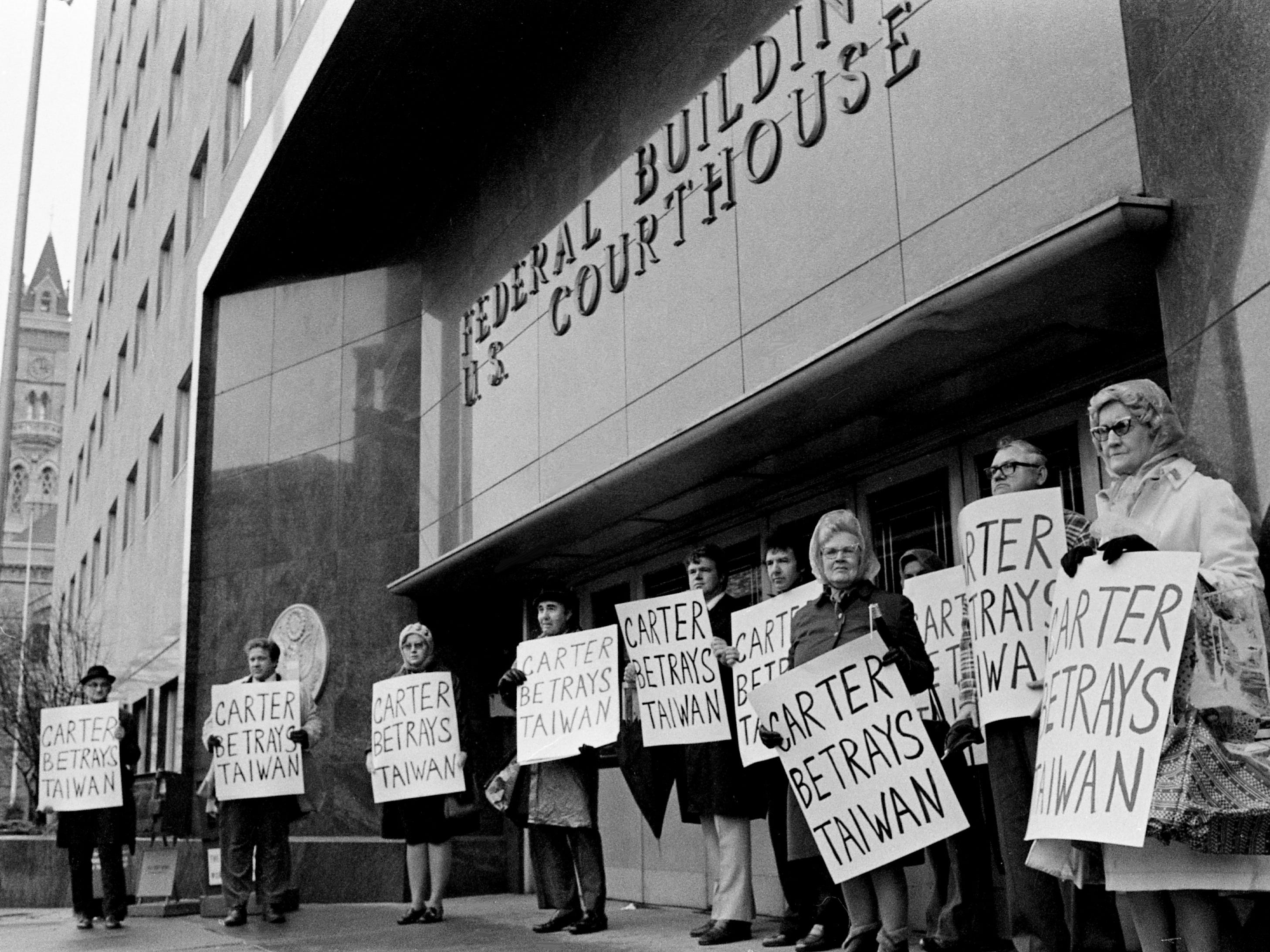 "Holding their ""Carter Betrays Taiwan"" hand-lettered signs, the Rev. Mel Perry, fourth from left, and some members of his congregation gather outside the Federal Courthouse on  Jan. 1, 1979, to protest the normalization relations between U.S. and the People's Republic of China."