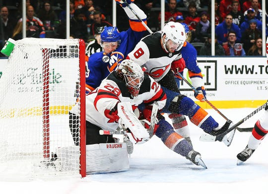 Jan 17, 2019; Uniondale, NY, USA; New Jersey Devils defenseman Will Butcher (8) and New York Islanders center Casey Cizikas (53) fall into Devils goaltender Mackenzie Blackwood (29) during the second period at Nassau Veterans Memorial Coliseum.