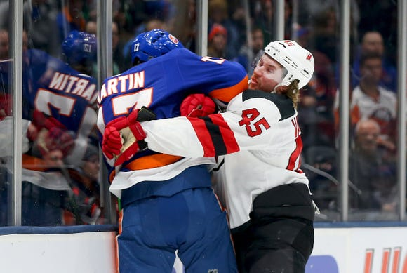 Jan 17, 2019; Uniondale, NY, USA; New Jersey Devils defenseman Sami Vatanen (45) and New York Islanders left wing Matt Martin (17) battle for position during the second period at Nassau Veterans Memorial Coliseum.