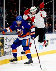 Jan 17, 2019; Uniondale, NY, USA; New Jersey Devils center Pavel Zacha (37) checks New York Islanders right wing Cal Clutterbuck (15) during the second period at Nassau Veterans Memorial Coliseum.